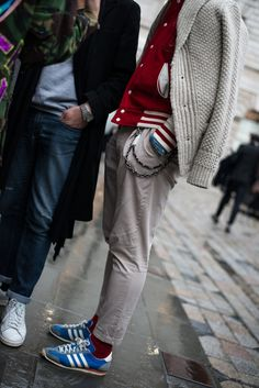 Shop this look for $137:  http://lookastic.com/men/looks/shawl-cardigan-and-varsity-jacket-and-chinos-and-socks-and-low-top-sneakers/1204  — Grey Shawl Cardigan  — Red Varsity Jacket  — Grey Chinos  — Red Socks  — Blue Low Top Sneakers