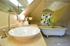 Give us a week and we'll design your perfect bathroom remodel, just like this attic-style bathroom renovation. This bright and eclectic design bathroom features a vessel sink, gooseneck faucet and clawfoot tub. Stained glass windows add a bit of vintage to the neutral bathroom design. Contact us for help with your bathroom remodel ideas! #OneWeekBath #Vintage #Bathroom