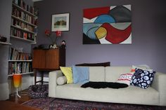 The walls are painted Farrow and Ball Calluna and the feature wall is in Brassica. The living room