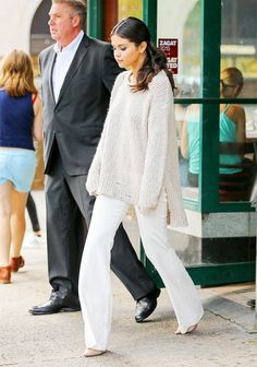 Selena Gomez wears a neutral billowy sweater, white flare jeans, and tan leather pointed-toe pumps