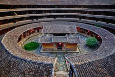 """Chine, Province du Fujian, village de Chuxi, maison forteresse en terre et en bois où logent les membres d'une meme famille de l'ethnie Hakka, inscrit au patrimoine mondial de l'Unesco // China, Fujian province, Chuxi village, Tulou mud house. well known as the Hakka Tulou region, in Fujian. In 2008, UNESCO granted the Tulou """"Apartments"""" World Heritage Status, siting the buildings as exceptional examples of a building tradition and function exemplifying a particular type of communal living… Monuments, Cool Places To Visit, Places To Go, Chinese Buildings, China Architecture, Mud House, Photo D Art, Old Building, China Travel"""