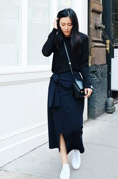 A black sweater is worn with a wrap skirt, sneakers, and a black bag