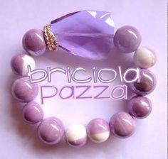 Bracciale elastico realizzato con perle in ceramica bicolore, gemma in resina ed elementi in metallo.