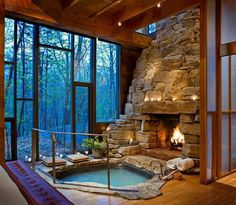 Bathroom of my dream! Except I would have a big old solid free standing bath with feet and no railing. AMAZING built in rocky wallface and fireplace.