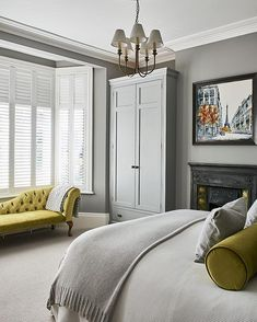 A modern cityscape (by Nigel Cooke at Wyecliffe Galleries) and lime-green accents lift the neutral palette in this comfortable bedroom, designed by and belonging to interior designer Emma Collins. #bedroom #interior #interiordesign #grey #limegreen Photograph by Jonathan Gooch