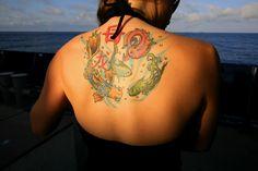 https://flic.kr/p/6u1WJB | tattoo | A bright tattoo decorates a young woman's back.