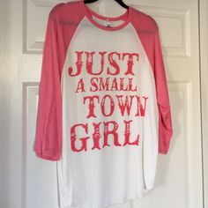 """Pink """"Just A Small Town Girl"""" This a cute pink shirt with the words """"Just a small town girl."""" Tag says 2X but can be worn loose by a large to XL sized. Brand new. G&G Tops Tees - Long Sleeve"""