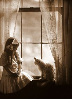Sepia - little girl and cat sitting on the window ledge