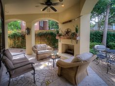 Covered back patio features tiled floor with decorative inlays, recessed lighting, two custom gas light fixtures, wood-burning fireplace, TV cabinet with retractable doors, stainless grill, wet bar & adjacent loggia area with beautiful wall sconces.