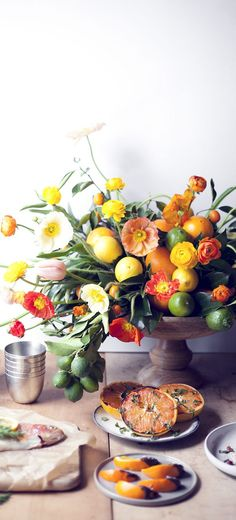 To serve as a vibrant example of how fruits can lend a fresh, cheery look to floral arrangements—and to show that cold-weather brides needn't shy away from splashy, summery hues—Holly Heider Chapple, the Beltway's best florist, created an eye-catching centerpiece composed of dense citrus clusters balanced by delicate Icelandic poppies and sprightly tulips in harmonizing hues.