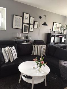 Vardagsrum, svart soffa, vit-grå randiga kuddar, posters, rosa liljor.
