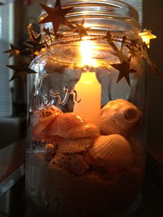 """Mason jar, seashell candle I made and used for our wedding.    Glued an emergency candle to the bottom, added 1"""" of white play sand.   Surrounded the candle with seashells with our names on them, topped it with foil star garland.   Absolutely PERFECT with minimal cost."""