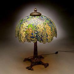 """Lampara de Mesa """"Laburnum""""""""Laburno"""" La colgantes ramas  en flor del amarillo laburno estan sobre una base de bronce que representa las raices de los arboles de flor, auqnue fue  conocida como  """"Bird Skeleton Base""""o """"Base de Esqueleto de Pajaro"""". Mide 68,5 cm de alto y 56 de diametro. En 1906 la pantalla costo 175$ y la base 90$. Takeo Horiuchi la adquirio  en Sotheby´s  New York el11/6/1992 para su colección del efimero museo japones Louis C Tiffany Garden Museum, cerrado por miedo a ser…"""