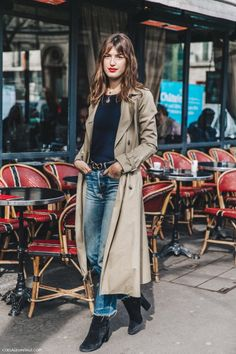 Trench coat, black top, layered necklaces, suede ankle boots, belt, red lip