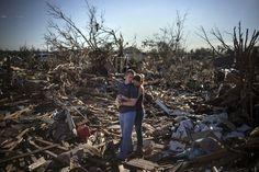 Una pareja se detiene entre los escombros que quedaron de un miembro de familia un día después del tornado que devastó la ciudad Moore, en Oklahoma.