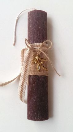A Greek Easter candle decorated with a gold olive branch, natural rope and ribbons. The candle is oval shaped, lightly scented and it measures 22cm or 8.66inch in height. The candle/lambada comes in a delicate hand decorated gift box.