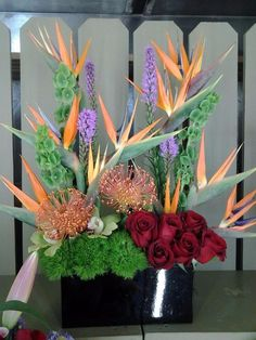 This arrangement includes, Roses, Birds of Paradise and Green Bell.