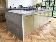 Penge, Beckenham, Kent. Bespoke standard grey straight cast in-situ 5m polished concrete kitchen worktop 60mm thick, sink and hob cut-outs. Sloping drainer and island with seamless waterfall end panel.