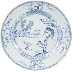 Très grand plat peint en bleu sous couverte en porcelaine de Chine de la Compagnie des Indes d'époque Yongzheng Très grand plat peint en bleu sous couverte, sur le bassin d'un paysage lacustre avec au premier plan un saule pleureur et au second plan, sur un tertre, une pagode près d'un rocher percé et deux arbres