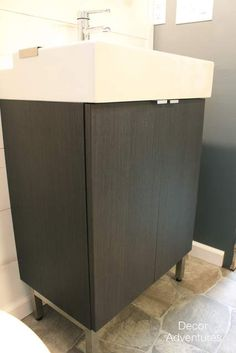 In a basement bathroom renovation we installed a Lillangen Ikea cabinet and sink, and Rorskar Ikea facuet. New bathroom vanity. Corner Bathroom Vanity, Basement Bathroom, Ikea Lillangen, Loft Ensuite, Ikea Cabinets, Wood Trim, Simple Bathroom, Bing Images, Storage