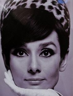 """The actress Audrey Hepburn photographed by Douglas Kirkland at the Studio de Boulogne in Paris (France), for the publicity of her new movie """"How to Steal a Million"""", in November 1965. Audrey was wearing: Hat: Givenchy (model pillbox lined with leopard skin, of his haute couture collection for the Autumn/Winter 1965/66)."""
