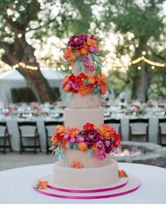 Tall, round ivory wedding cake with bright pink and orange flowers inspired by the desert setting by Ana Parzych Custom Cakes // Mel Barlow & Co