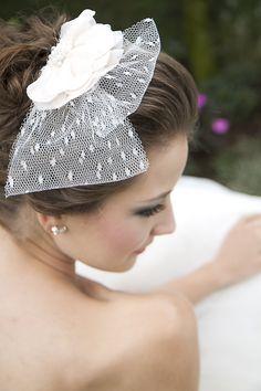 Tiara Tati para noivas, se adapta a penteados de cabelos meio presos ou coques. Feito com uma linda flor em camadas de cetim e chiffon, com detalhes pérolas e cristais e um delicado voilette de tule poá desprit, R$ 180,00.