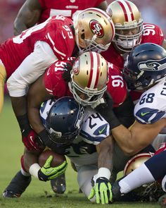 Seahawks running back Marshawn Lynch is tackled by San Francisco 49ers defensive tackle Ray McDonald (91) and linebacker Aldon Smith (99) for a 2-yard gain in the first quarter at Candlestick Park in San Francisco on Oct. 18, 2012