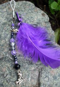 Charm - Black and Purple with witch - approx 9cms    Charm to hang from you handbag, purse, phone, in your home or car in fact wherever you want to dangle it from!    This charm has:    Black & purple feathers    A witch on a broomstick charm    A large silver bell    Black and purple beads    £3.99 plus p    For more designs see our website Magpies and Moonbeams on facebook