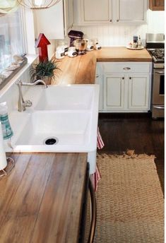 Wood countertops and white cabinets for the kitchen makeover? Ooh! And black knobs.