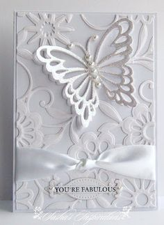 handmade card from Sasha's Inspirations ... all white ... die cut butterfly with pearl body rests on embossing folder bed of flowers ... knotted satin ribbon ... wonderful card!!