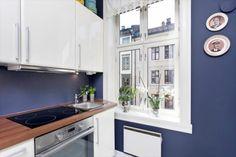 lila-blaue Wandfarbe, weiße Hochglanz Fronten und Holz Arbeitsplatte