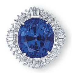 A TANZANITE AND DIAMOND RING   Set with an oval-shaped tanzanite weighing 16.67 carats, within a brilliant and tapered baguette-cut diamond ballerina surround, mounted in platinum