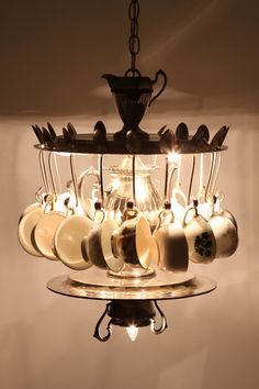 Eighteen vintage teacups dangle from an arrangement of vintage silver serving trays, utensils and the teapot itself, as seven lights illuminate the scene ~ Gorgeous! I wonder if my son could make something like this out of thrift store, garage sale, estate sale, etc..., items?!