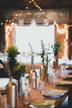 Rustic Style Wedding Decoration tip - add a golden glimmer to your barn wedding by using fresh herbs and greenery inside empty wine bottles painted gold. More rustic wedding ideas if you click on the photo.