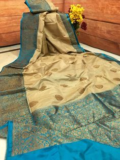 Be the glamorous diva of everyone's eyes dressed in this pretty contemporary yet classy Deep Beige, Deep Sky Blue color combination Tussar Banarasi Silk Saree. Beautified with classic Antique Gold Zari weaving Banarasi motifs all over the body, floral bel border on blue base and brocade-like pallu gather the trend and