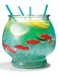 Cocktail recipe for a The Fish Bowl made with ½ cup Nerds candy  ½ gallon goldfish bowl  5 oz. vodka  5 oz. Malibu rum  3 oz. blue Curacao  6 oz. sweet-and-sour mix  16 oz. pineapple juice  16 oz. Sprite  3 slices each: lemon, lime, orange  4 Swedish gummy fish