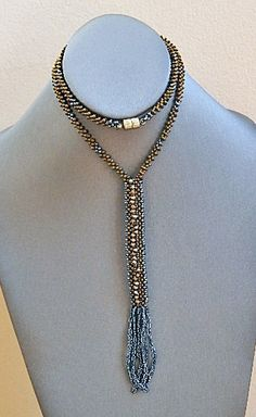 This necklace is 24 inches long (the chain). The pendant part is 5.5 inch long by 0.5 inches wide. The chain is a Right Angle Weave stitch using peanut
