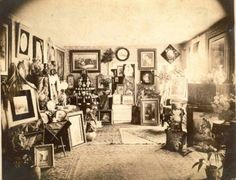 A period photo of a Victorian interior. Note the numerous framed pictures on the wall and the decorative objects on every available surface. Scroll down to see more room settings in our gallery of Victorian interiors. |