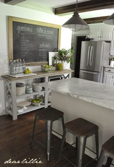 Farmhouse kitchen makeover. Exposed beams, marble countertops, giant chalkboard, industrial lighting, stainless steel appliances, white cabinets, and some open shelving.
