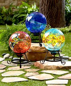 """This Colorful Glass Ball on Stand gives your yard a mystical touch. It makes an interesting art piece in the midst of your flowers and plants. Every 9"""" dia. ball has unique markings, which add to its beauty. The black metal base easily rests on the groun"""
