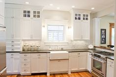 black honed counter tops, farmhouse sink, marble backsplash, to the ceiling cabinetry.
