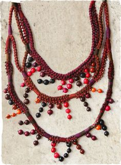 The multi-strand necklace is comprised of colorful beads and seeds, artfully strung on berry-hued crocheted pima cords.