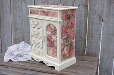 Hand painted and decoupaged vintage jewelry box. Solid wood, painted a soft ivory and lightly distressed with decoupage in shades of pink and rose and finished with a protective clear coat. The interior is dark ivory colored velveteen with 4 drawers, 3 open and 1 with a ring holder, the top opens to 5 compartments. The door is decoupaged on the inside and outside and opens to a necklace carousel and mirror. The drawer and door pulls are accented in gold. Felt pads have been added to the…
