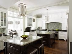 We like a lot about this kitchen.  Like the floors, cabinet style, contrast between white cabinets and dark island; dislike the brackets under the cabinetry, and backsplash (small tiles).