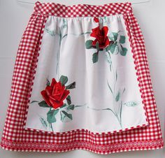Link broken--but what a beautiful apron--cross stitch on gingham, with a rose-patterned fabric overlay. Wow! Would be perfect for the holidays.