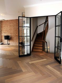 This room is Amsterdam: Antique brick wall, super steep stairs and Hakwood ., This room is Amsterdam: Antique brick wall, super steep stairs and Hakwood (Dutch) designed and manufactured herringbone pattern. Home, House Styles, Herringbone Wood Floor, House Design, New Homes, Black Interior Doors, Engineered Flooring, House Interior, Doors Interior