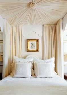 Canopy bed + monogrammed linens.