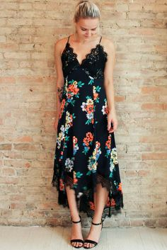 We're loving dark florals for Fall! The Nightingale Dress features a moody all-over floral pattern accented in contrasting black lace, point hi/low hem and adjustable criss cross back. Throw on a velv