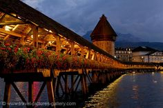 Switzerland - Lucerne - Kapellbrücke (Chapel Bridge) over the Reuss River at night - one of Europe's oldest wooden bridges and landmark of Lucerne.  Inside the bridge are a series of paintings from the 17th century, depicting events from Lucerne's history. Much of the bridge, and the majority of these paintings, were destroyed in a 1993 fire, though it was rebuilt.